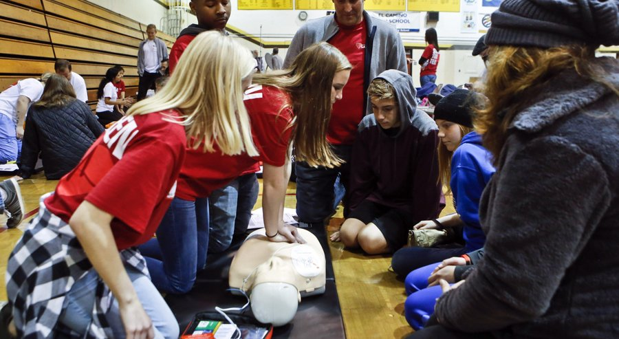 Oceanside teacher Doug Musgrove (top center) looks on as Callie Zellers demonstrated CPR techniques during training for teenagers and their parent at the free youth heart screening at El Camino High School on Sunday.